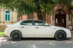 有黑合金轮子的白色阿尔法・罗密欧159汽车在街道上停放了 库存照片