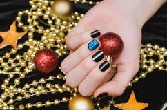 有黑和蓝色钉子设计的美好的女性手 圣诞节修指甲 免版税图库摄影