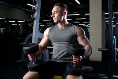 有黑哑铃的肌肉人坐在健身房的长凳 图库摄影