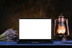 有黑屏的一台膝上型计算机在一张蓝色木桌上站立 免版税图库摄影