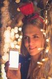 有黑屏聪明的电话和圣诞灯装饰的女性 技术和假日概念 免版税库存图片
