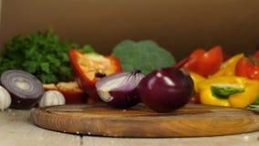 有黑手套的厨师切在一半的红洋葱在一个木切板,弓被削减成两个一半摇摆  股票录像