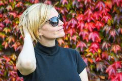 有黑握她的胳膊的太阳镜和衬衣的愉快的轻松的妇女在她的头背面 免版税库存照片