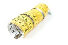 有黑数字的黄色缝合的测量的磁带在白色背景 免版税库存照片