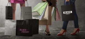 有黑星期五纸袋文本的购物妇女 免版税库存图片