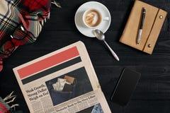 有黑显示的巧妙的电话在木背景 报纸和咖啡在木桌上 顶视图 图库摄影