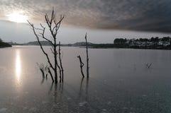 有黑暗的云彩的冻湖 免版税库存照片