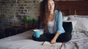有黑暗的卷发的可爱的少妇是阅读书转动的页和享用文学坐与杯子的床 股票录像