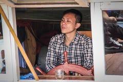 有黑暗的皮肤的Asian上尉人驾驶有一个木海方向盘的一艘船 库存照片
