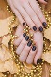 有黑暗的紫色钉子设计的美好的女性手 免版税库存照片