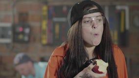有黑暗的长发、盖帽和安全玻璃的少女木匠的 女性吃苹果 手制造业 股票视频