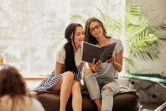 有黑暗的长发的,佩带的偶然成套装备,看看两个年轻亭亭玉立的女孩一本书在一现代咖啡馆 免版税库存照片