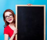 有黑板的红头发人妇女 免版税图库摄影