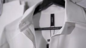 有黑标签的白色衬衫在黑挂衣架在时尚演播室 股票视频