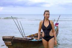 有黑比基尼泳装和小船的妇女在海滩 库存照片