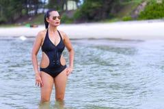有黑比基尼泳装展示的妇女性感在海滩 库存图片