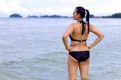 有黑比基尼泳装展示的妇女美好在海滩 免版税库存照片
