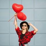 有黑玻璃和帽子的一名妇女拿着红色球 免版税图库摄影