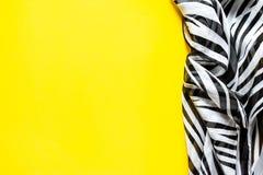 有黑白条纹的轻的典雅的透明气体披肩有斑马装饰品顶视图黑色颜色背景 免版税图库摄影