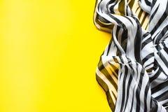 有黑白条纹的轻的典雅的透明气体披肩有斑马装饰品顶视图黑色颜色背景 免版税库存图片