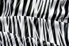 有黑白条纹的轻的典雅的透明气体披肩有斑马装饰品顶视图黑色颜色背景 免版税库存照片
