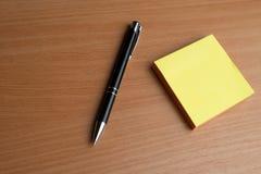 有黑笔的笔记本,在书桌上的五颜六色的在书桌上的笔记薄,玻璃有笔的和咖啡,有col的键盘 库存图片