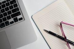 有黑笔的笔记本,在书桌上的五颜六色的在书桌上的笔记薄,玻璃有笔的和咖啡,有col的键盘 免版税库存照片