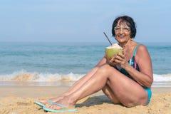 有黑色头发的一名年长妇女由海坐一好日子 游泳衣的一名妇女用椰子微笑着 免版税库存图片