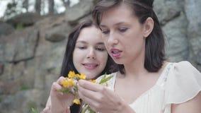 有黑色头发辫子花冠的画象两美女在与绿色植物的巨大的石头附近 可爱的女朋友 影视素材
