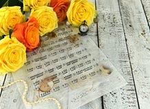 有黑蜡烛的箱子、装饰和英国兰开斯特家族族徽在巫婆tableYellow玫瑰与装饰,怀表和音乐纸张笔记 库存照片