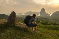 有黑袋子的亚裔夫人坐岩石神色在山和河视图 库存图片