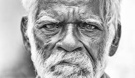 有黑褐色的老印地安贫困者起了皱纹面孔和白发和白色胡须,严肃或哀伤 黑色白色 免版税图库摄影