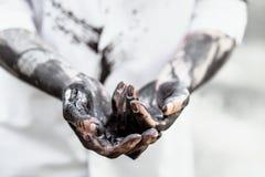 有黑金的油的肮脏的手 免版税库存图片