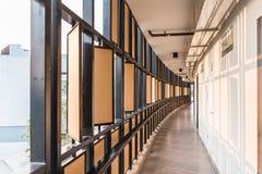 有黑钢和木板材的旅馆走廊有橙色光的在白色墙壁上的被投下的阴影在清迈,泰国 免版税图库摄影