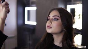 有黑马尾的化妆师使用做完成的浪花和轻轻地喷洒它在她的从a的客户的面孔 股票录像