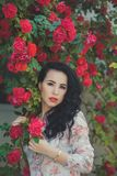 有黑黑暗的卷发的惊人的神秘的夫人妇女变粉红色佩带设计师女装设计师衬衣和蓝色sho的面颊噘嘴深红嘴唇 免版税库存照片