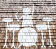 有鼓的一个人在木墙壁上 免版税库存图片