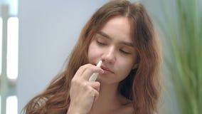 有鼻塞的不健康的女孩使用冷的治疗的鼻孔喷射 影视素材