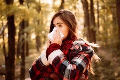 有鼻子刮水器的少妇在秋天树附近 病的女孩以流鼻水和热病 显示打喷嚏秋天的病的妇女 免版税库存图片