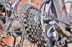 有齿轮和链子的新的卡式磁带在老灰色自行车的后轮 库存图片