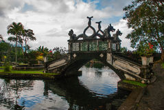 有龙四个雕象的一座人为桥梁与扭转的尾巴的, Tirta Gangga公园, Karangasem,巴厘岛,印度尼西亚 免版税库存照片