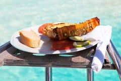 有龙虾的板材在反对加勒比海的天蓝色的水的背景的一条游艇 库存图片