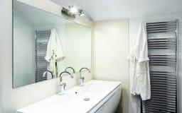 有龙头的现代卫生间在白色内阁 图库摄影