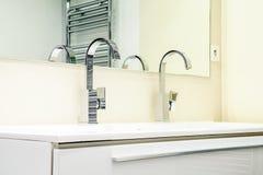 有龙头的现代卫生间在白色内阁 库存图片