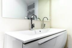 有龙头的现代卫生间在白色内阁 免版税库存图片