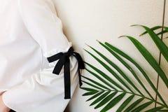有黑串蝶形领结样式细节的长的白色袖子 关闭时髦时尚和绿色叶子 免版税库存照片