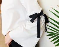 有黑串蝶形领结样式细节的长的白色袖子 关闭时髦时尚和绿色叶子 免版税库存图片