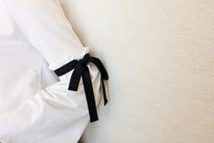 有黑串蝶形领结样式细节的长的白色袖子 关闭时髦时尚 免版税图库摄影