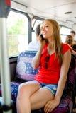 有去乘公共汽车的智能手机的微笑的十几岁的女孩 免版税图库摄影