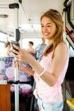 有去乘公共汽车的智能手机的微笑的十几岁的女孩 库存照片